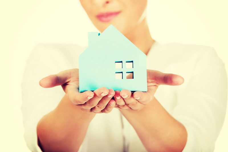 woman holding blue home cutout